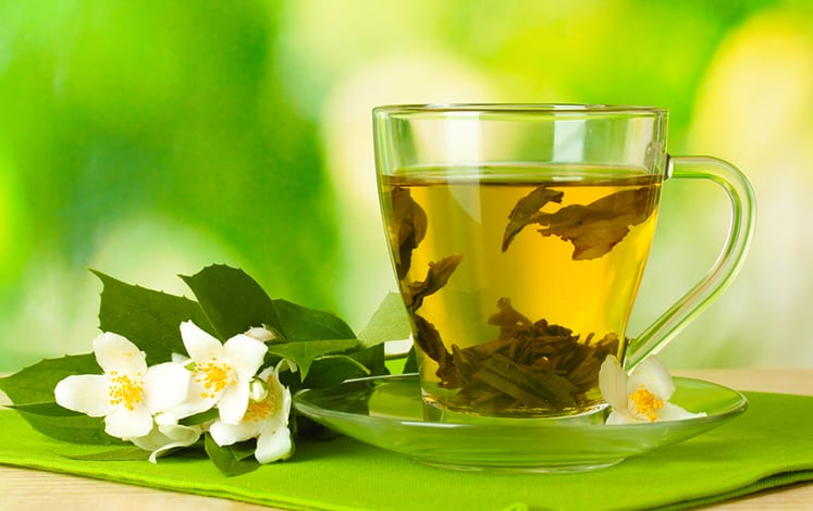 cup of green tea with jasmine flowers on wooden table on green b